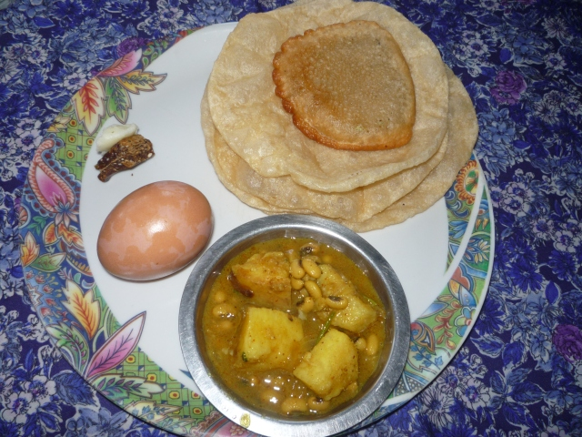 Magghe Sankranti breakfast (from left clockwise): hard boiled egg, til ko laddu with ghee, deep fried puri, pancake with fennel seeds and sakhar-khand curry.