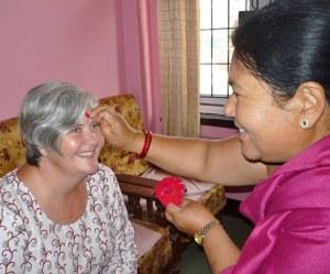 Krishna Maya applying tika