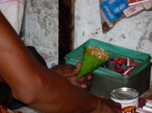 Preparation of a betel leaf - the betel nut is grated, mixed with water and the paste smeared onto a leaf.  The leaf with the betel paste is chewed.  Also sold are single cigarettes with one go of the lighter plus a mint sweet to clear the breath - how civilized!