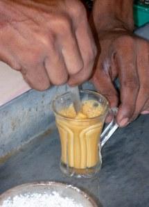 Vigorous stirring of the condensed milk into the red tea, to make milk tea.