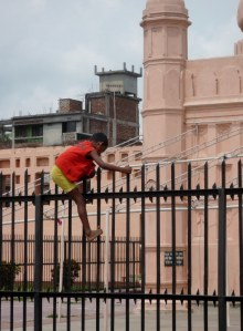 A kid clambouring over the mosque fence into the fort grounds to retrieve his cricket ball.  Same old all over the world!