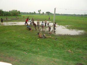 After a deluge, the kids mucking around (literally) on the football pitch