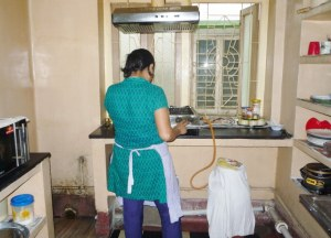 Rajashi at the 4-burner in her kitchen, the washing area to the left at ground level.