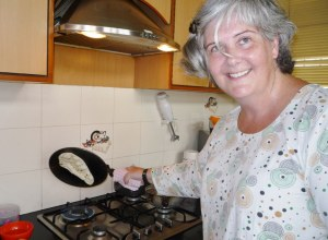 Water side down, lay it on a lighting hot pan.  The water adheres the dough to the pan, making it safe to turn the dough up side down over the naked flame.  Within a minute the naan is ready.  Here's me looking relieved my naan stuck to the pan!