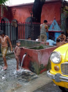 Daily wash at the communal water pump on the side of the street
