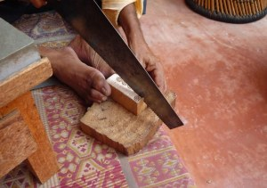 He uses his feet to steady the block of wood to saw of the small flower. Then planes and sandpapers it for the final product.