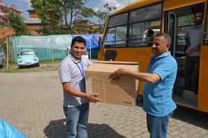 Shyam (left) is SIRC's accountant but it is all hands on deck these days.  Shyam is taking delivery of folded gauze that has been donated by the Rato Bangela School.  The school bus was used to deliver the many many boxes.