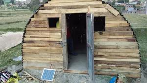 The finished shelter, complete with solar panel for electricity.  The door and wood were salvaged from the collapsed home.