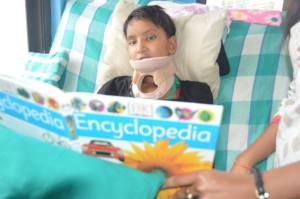 Young patient with spinal cord injuries enjoying a book from the small library in the ward