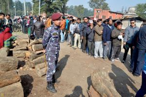 Locals patiently line up to buy wood, under the watchful eye of a member of the Nepalese Army
