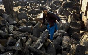Woman assessing the stockpile of wood at Pashupatinath Temple.