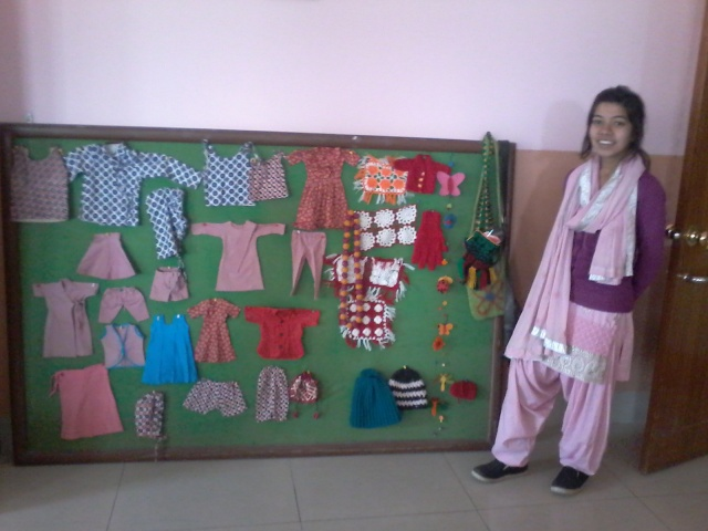 A BMKF scholar impressed with the array of babies clothes made by SIRC patients as part of their vocational training program