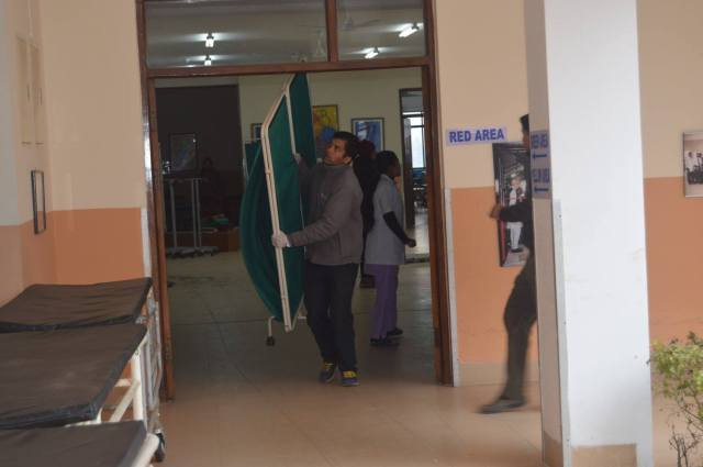 Keshab setting up the privacy screens for the treatment locations, prior to the arrival of the injured