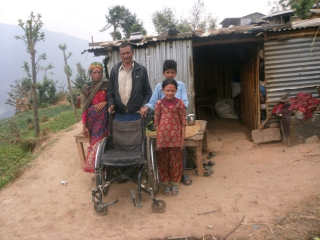 Bishnu Khadka and his family outside their temporary home. Photo credit Prajwal Ghimire