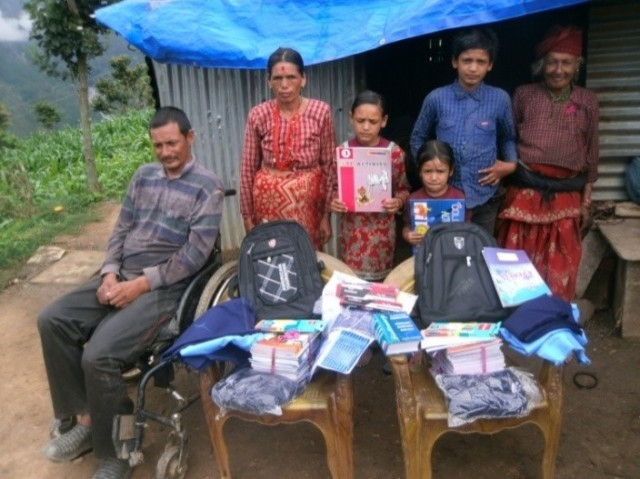The two Khadka children aged 10 and 6 years old with their school books, stationery and uniforms in advance of the school year.  Photo credit Prajwal Ghimire.
