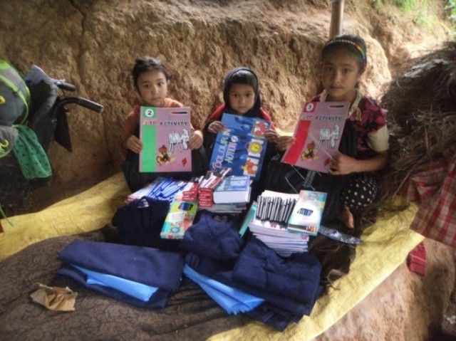 The three Pandey children aged 10, 8 and 6 years old with their school books, stationery and uniforms in advance of the school year.  Photo credit Prajwal Ghimire