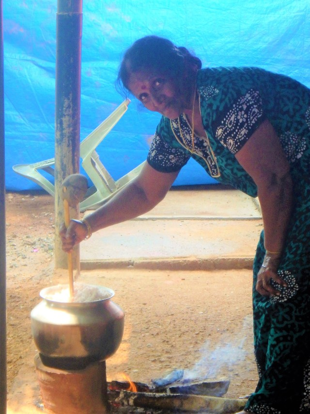 Granny making paalchoru (milk rice) for breakfast, it being the 1st day of the month. Notice the earthen pot stand allowing for the wood to be burned underneath.
