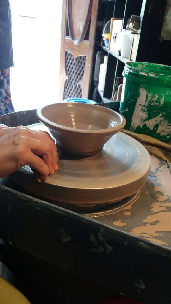 Using a scrapper-like tool, the base of the bowl is trimmed to make it easier to cut through it with the wire. The wheel is still spinning!